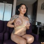 Jayla plays with her big boobs while sitting naked on the couch