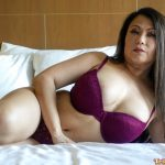 Sexy milf lays on the bed wearing bra and panties